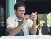 Hispanic man using electronic organizer at outdoor cafe — Stock Photo