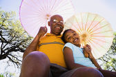 African American grandfather and granddaughter with parasols — Stock Photo