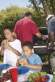 Boys eating hamburgers at backyard barbecue — Stock Photo