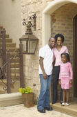 Young African parents with daughter in entrance of house — Stock Photo