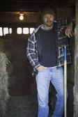 Man smiling in barn doorway with pitchfork — Stockfoto