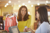 Woman purchasing clothing — Stock Photo