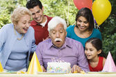 Senior Hispanic man blowing out birthday candles with family in park — Stock Photo