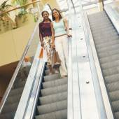 Girlfriends descending mall escalator — Φωτογραφία Αρχείου