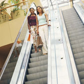 Girlfriends descending mall escalator — ストック写真