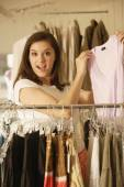 Woman holding up shirt at clothing store — Foto de Stock
