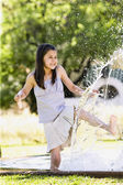 Young Hispanic girl playing in water outdoors — Stock Photo