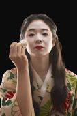 Asian woman in ethnic clothes applying makeup — Stock Photo