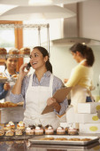 Woman talking on phone while working in bakery — Stock Photo