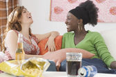 Two women laughing on sofa — Stock Photo
