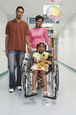 African girl smiling in wheelchair with parents in hospital — Stock Photo