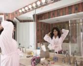 Hispanic woman looking in bathroom mirror — Stock Photo