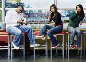 Three teenagers on stools with cell phones — Stock Photo