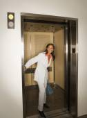 African woman holding elevator open — Stock Photo