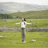 Young woman standing on a rock with her arms outstretched in rural location — Stock Photo
