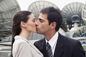 Hispanic couple kissing in front of satellite dishes — Stock Photo