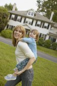 Mother giving young daughter piggyback ride outdoors — Stock Photo
