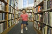 Girl running down aisle of library — Stock Photo