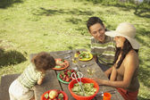 Familie eten op een picknicktafel buiten — Stockfoto