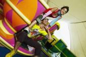 Teenage Hispanic couple sitting in teacup carnival ride — Stock Photo