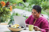 Middle-aged African woman using laptop outdoors — Stock Photo