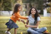 Mother and daughter blowing bubbles outdoors — Stock Photo