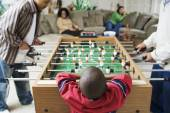Family watching foosball game — Stock Photo