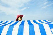 Hispanic woman standing behind beach sun shade — Stok fotoğraf