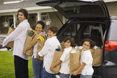 Hispanic family unloading grocery bags from car — Stock Photo