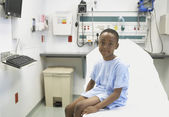 African boy sitting on edge of hospital bed — Stock Photo