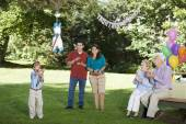 Family watching Hispanic boy hitting pinata at birthday party — Stock Photo