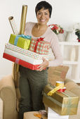 Woman holding gifts and wrapping paper — Stock Photo