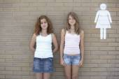 Two teenage girls leaning against wall next to restroom sign — Foto de Stock