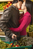 Asian couple kissing in produce section of grocery store — Stock Photo