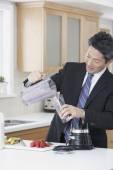 Asian businessman making fruit smoothie — Stock Photo