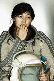 Female astronaut holding a helmet biting her finger nails — Stock Photo