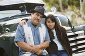 Hispanic father and daughter sitting on classic car — Stock Photo