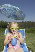 Young girl drinking juice in a lawn chair — Stock Photo