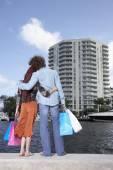 Multi-ethnic couple holding shopping bags — Stock Photo