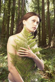 Woman standing with branch covering naked upper body — ストック写真