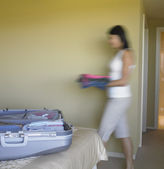 Blurred motion shot of woman packing suitcase — Stock Photo