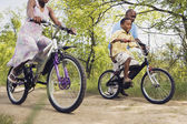 African grandfather teaching grandson to ride a bicycle in park — Stock Photo