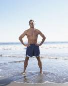 Man standing with hands on hips at the beach — Stock Photo