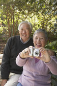 Senior Asian couple sitting on a park bench with a digital camera — Stock Photo
