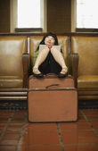 Woman sitting with luggage and book — Stock Photo