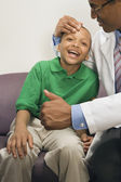 Doctor giving thumbs up to smiling African boy — Stock Photo