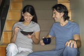 Multi-ethnic couple having breakfast on stairs — Foto Stock