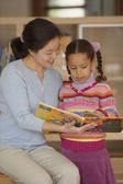 Female teacher reading book with student — Stock Photo