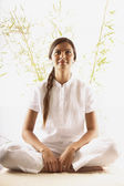 Young woman sitting on the floor meditating — Stock Photo