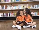 Two young sisters whispering in library — Stock Photo